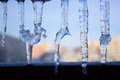 Dripping icicles against the sky. transparent icicle close up ag Royalty Free Stock Photo