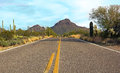 Drive through the sonoran desert highway runs leading to mountain peak Stock Image
