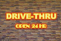 Drive thru neon signage in a brick wall Stock Photo