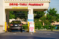 Drive thru pharmacy with a vehicle at the pickup window photographed from exterior of building Stock Photo