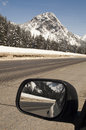 Driver checks rear view mirror motoring north cascades washingto a fresh covering of snow blankets mountains over the pass on i Stock Images