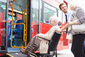 Driver helping senior couple board bus via wheelchair ramp looking at each other smiling Stock Image