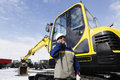 Driver operator standing front new bulldozer digger Royalty Free Stock Image