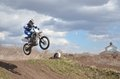 Driver standing on the mx motorcycle is flying over the motocross rider hill a background of blue sky Royalty Free Stock Photography