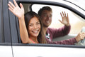 Drivers driving in car waving happy at camera young couple on road trip new interracial couple Stock Images