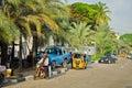 Drivers of yellow tuk tuks ply their trade around the port city