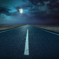 Driving on asphalt road at night towards the moon an empty Royalty Free Stock Photography