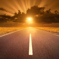 Driving on asphalt road at sunset towards the sun iv an empty Stock Image