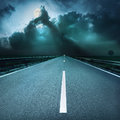 Driving on asphalt road towards oncoming stormy night at spooky Stock Photos