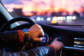 Driving a car at night man driving his modern car at night in a city shallow dof color toned image Royalty Free Stock Images
