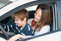 Driving a car smiling mother teaching her son how to drive Royalty Free Stock Image