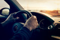 Driving a car at sunset - focus on speedometer Royalty Free Stock Photo