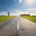 Driving on an empty old asphalt road through the agricultural fields Stock Photos