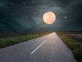 Driving on an empty road towards the moon Royalty Free Stock Photo