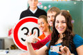 Driving instructor with his class school in and a female student driver looking in the camera in the background are traffic Royalty Free Stock Images