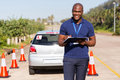 Driving instructor writing portrait of african american on clipboard Stock Photos