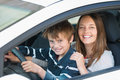 Driving lesson beautiful mother teaching her son how to drive a car Stock Images
