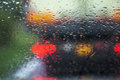 Driving in the rain weather conditions on the roads traffic blurred raindrops windscreen focus center blurring to smears Stock Images