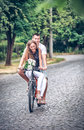 Driving of a young pair by bicycle down street Royalty Free Stock Photo