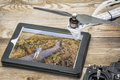 Drone aerial photography concept reviewing picture operator in a field on a digital tablet with a rotor and Stock Images