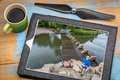 Drone aerial photography concept reviewing picture operator on a river shore on a digital tablet with a rotor Stock Photos