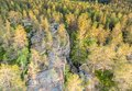 Drone photo of Northern Scandinavian forest in rocky mountains, big stones, yellow green trees at the end of summer - beginning of