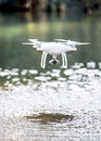 Drone quadcopter with camera flying above water. Royalty Free Stock Photo