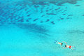 Drone view of couple snorkeling in clear blue sea water Royalty Free Stock Photo