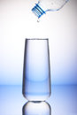 Drop of water falling from bottle into drinking glass Royalty Free Stock Photo