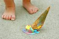 Dropped ice cream cone by child s feet a rainbow colored lays upside down on the sidewalk at the of a young Royalty Free Stock Image