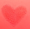 Drops of water in the form of heart on a red background Royalty Free Stock Photo