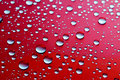 Drops of water on a red background droplets close up Stock Image
