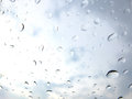 Drops of water on a window pane with cloudy sky in the background Stock Image