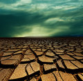 Drought land and storm clouds Royalty Free Stock Photo
