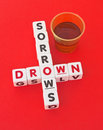 Drown your sorrows text and inscribed on small white cubes arranged crossword style with common letter o beside glass of brandy Royalty Free Stock Photo