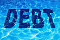 Drowning in debt business and finance concept with the word icon sinking under a sparkling reflection of blue pool of water as a Royalty Free Stock Image