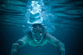 Drowning diving mature underwater tinted in blue image of a man crashing into the water with a panama hat surrounded by bubbles Royalty Free Stock Photo