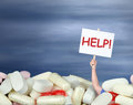 Drug abuse addiction chronic pain medication a huge pile of various pills with a man s hand coming out of the pills holding a sign Stock Image
