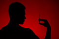 Drug addict standing on red background young man holding needle in hands Stock Images