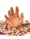 Drug addiction concept hand reaching up from pills Royalty Free Stock Image