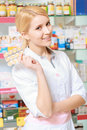 Druggist holds a blister of pills best treatment portrait young beautiful smiling pharmacist holding Stock Photos