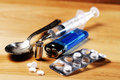 Drugs addiction syringe spoon pills bullet and lighter on the floor Stock Photos