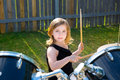 Drummer blond kid girl playing drums in tha backyard lawn Stock Photography
