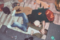 Drunk bearded man lying on floor in messy room Royalty Free Stock Photo