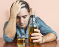 Drunk and depressed hispanic man suffering a headache with liquor bottle on table Stock Photography