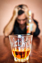 Drunk and depressed man addicted to alcohol portrait of a focused on the drink his face is out of focus Royalty Free Stock Image