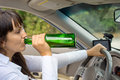 Drunk female driver in her car driving along the road gulping booze directly from the bottle Stock Photo