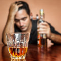 Drunk and lonely latin man holding a rum or whiskey bottle image focused on his drink Stock Image