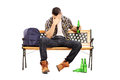 Drunk male teenager sitting on a bench and drinking beer isolated white background Royalty Free Stock Photos
