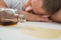 Drunk man with a bottle of liquor young sleeping on table Stock Photo